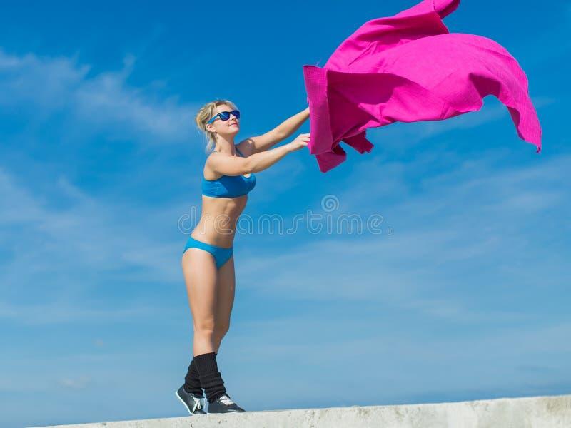 Idrottskvinna i blått vifta med för sportswear och för solglasögon av rosa färger s arkivbild