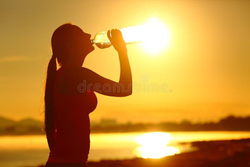 Idrottskvinna som dricker buteljerat vatten efter sport arkivfoto