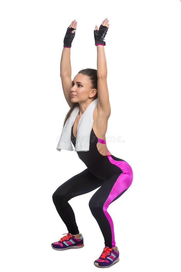 Idrottskvinna som gör squats arkivfoton