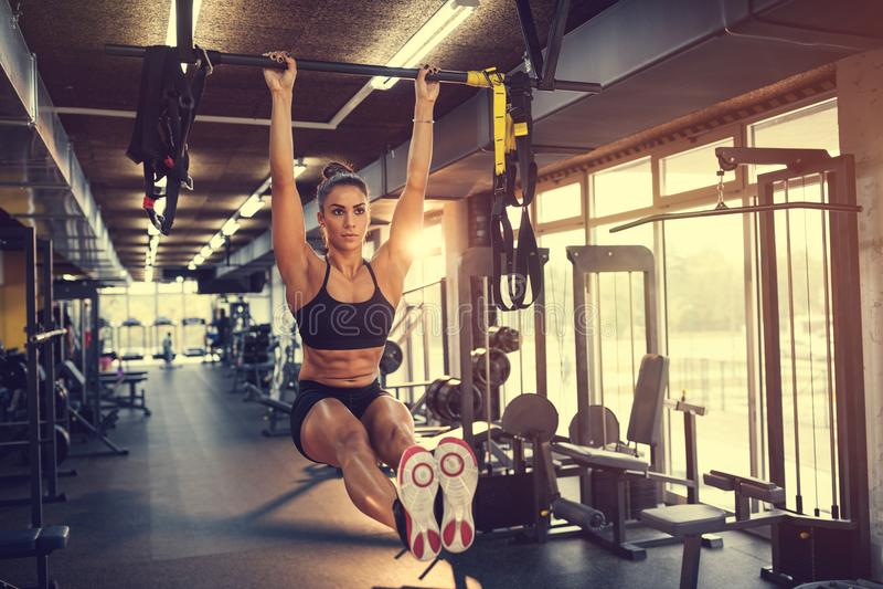 Idrottskvinna som lyfter upp på horisontalstång i idrottshall royaltyfri foto