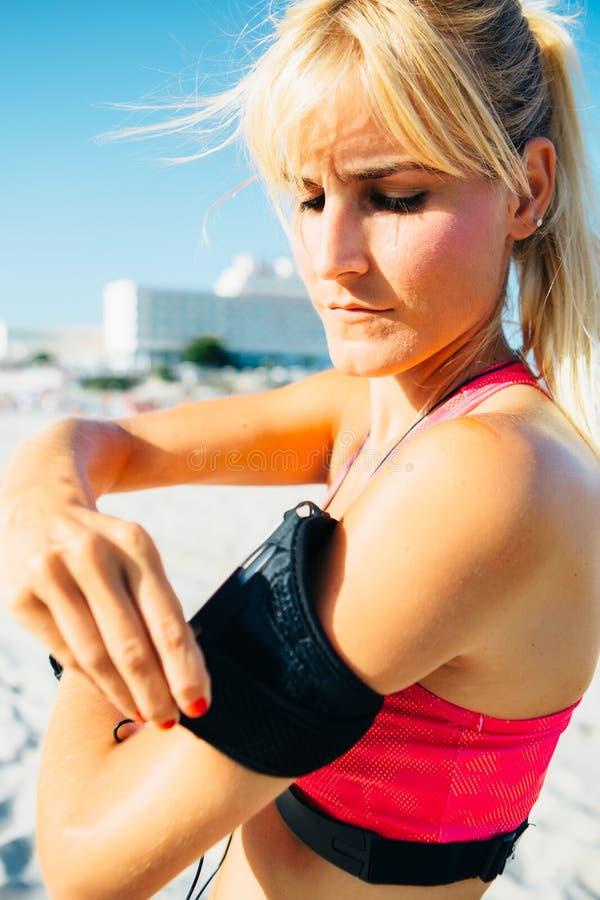Idrottskvinna som sätter armbindeln arkivbilder