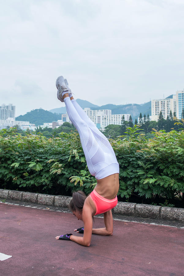 Idrottskvinnan som gör anseende för handstansyogaövning på hennes underarmen med raksträcka, lägger benen på ryggen banan i parke royaltyfri foto