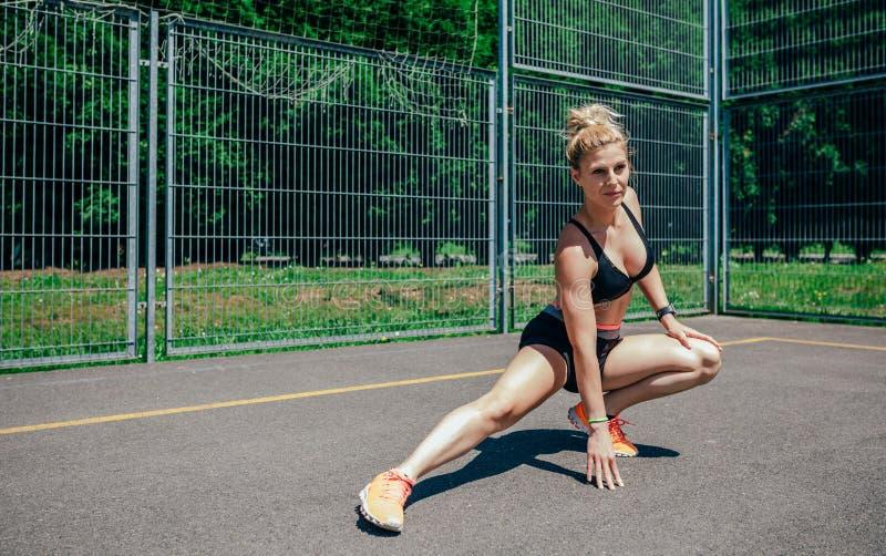 Idrottskvinnan som gör benet, sträcker arkivfoto