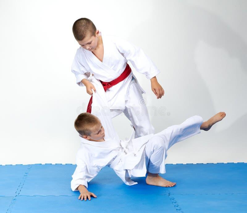 Idrottsmän som tränar judo kastar på blå mattor arkivbild