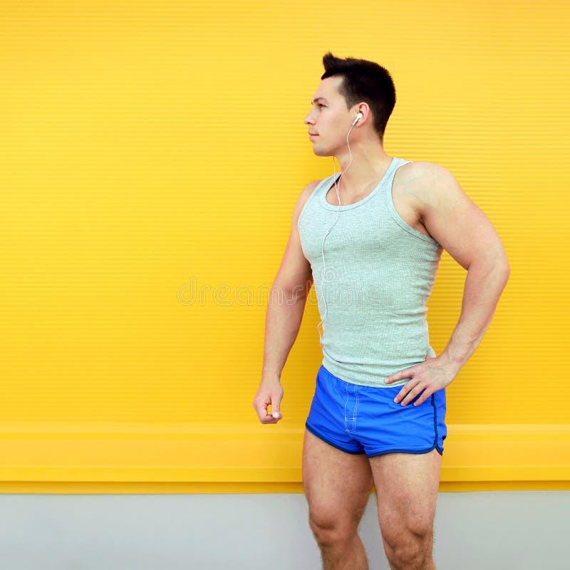 Idrottsman över färgrik gul väggbakgrund Kondition sportbegrepp, blickprofil fotografering för bildbyråer