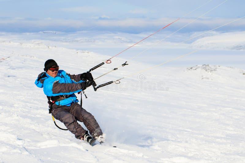 Idrottsman för ryttare för mandrakelogi med draken i himmelritter i snö på drakebräde Fritids- aktivitet, extrema aktiva sportar, royaltyfria bilder