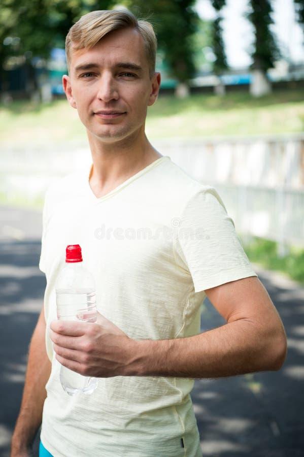 Idrottsman med den plast- flaskan på soligt utomhus- Törstig man med vattenflaskan på stadion Törstat och uttorkning Dricksvatten arkivfoton