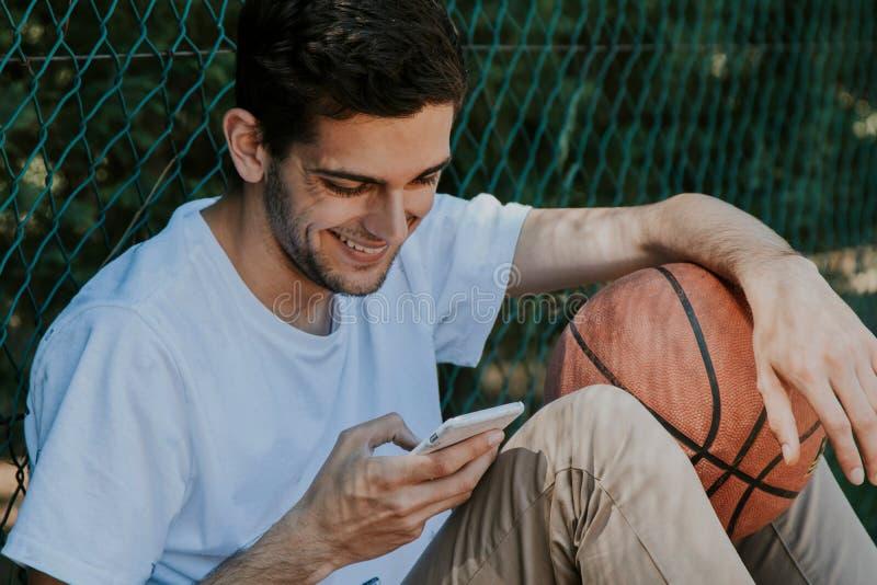 Idrottsman med mobilen, basket royaltyfri bild