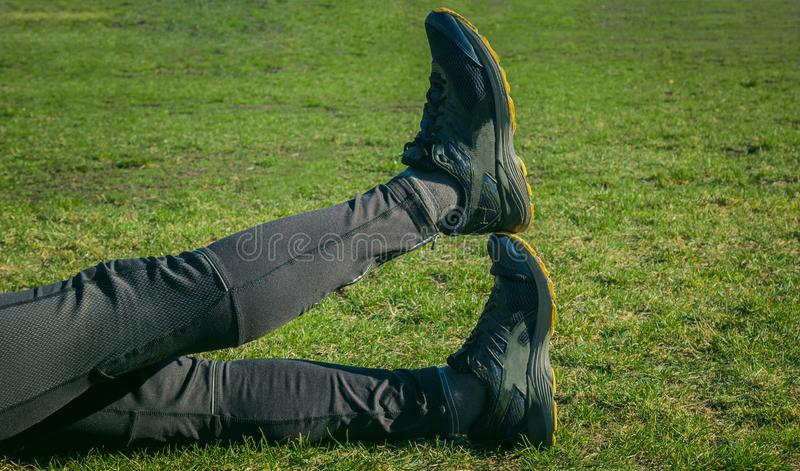 Idrottsman nen ben i damasker och gymnastikskor som ligger på jordningen på gräsmattanärbilden korsade ben utbildning på det fria arkivbild
