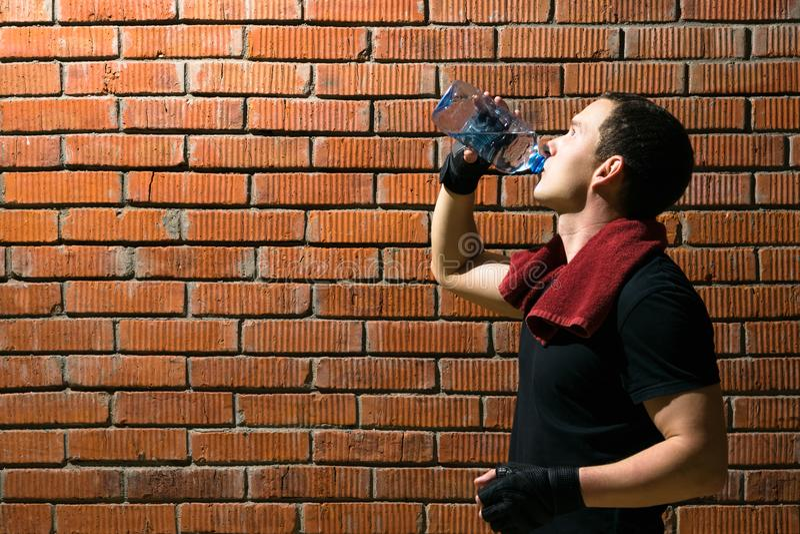 Idrottsman nen, efter kondition har klassificerat drinkvatten från en flaska på en bakgrund av en vägg för röd tegelsten arkivbilder