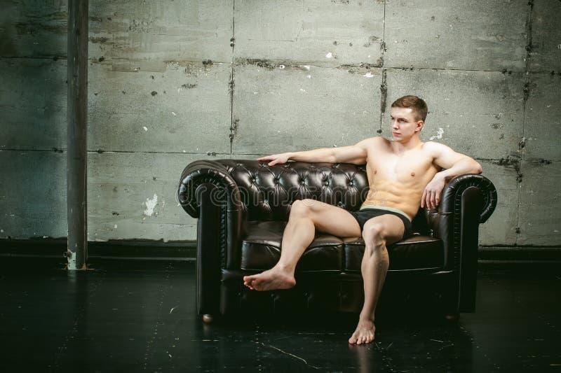 Idrottsman nen för kroppsbyggare för män för studiostående ung sexig, med en kal torso royaltyfria foton