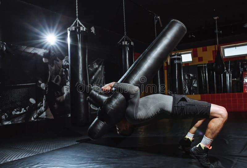Idrottsman nen gör kastet av attrappen, utbildningen av brottaren, idrottshallen för att slåss arkivfoto