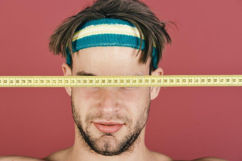 Idrottsman nen i utbildning Mannen med smutsigt hår har ögon som stängs med måttbandet royaltyfri foto