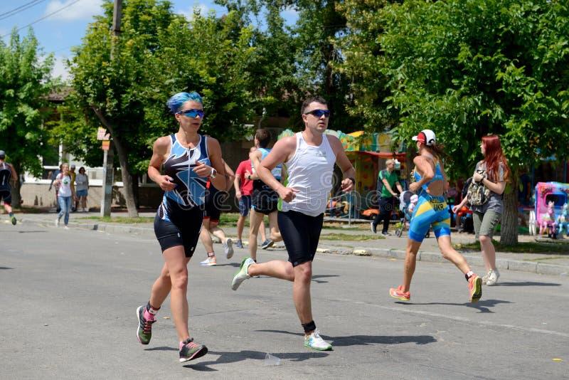 Idrottsman nen konkurrerar i rinnande del under internationell triathlonkonkurrens royaltyfri foto