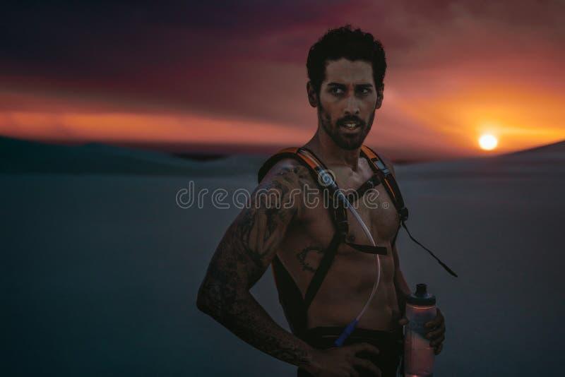 Idrottsman nen som har ett avbrott i öken på solnedgången royaltyfri foto