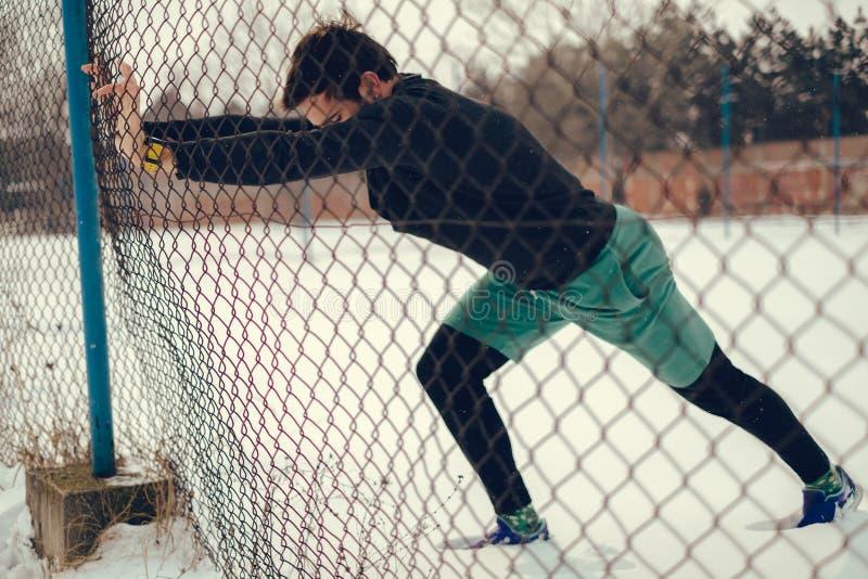Idrottsman nen som sträcker kalvar på staketet på en snöig dag arkivbild