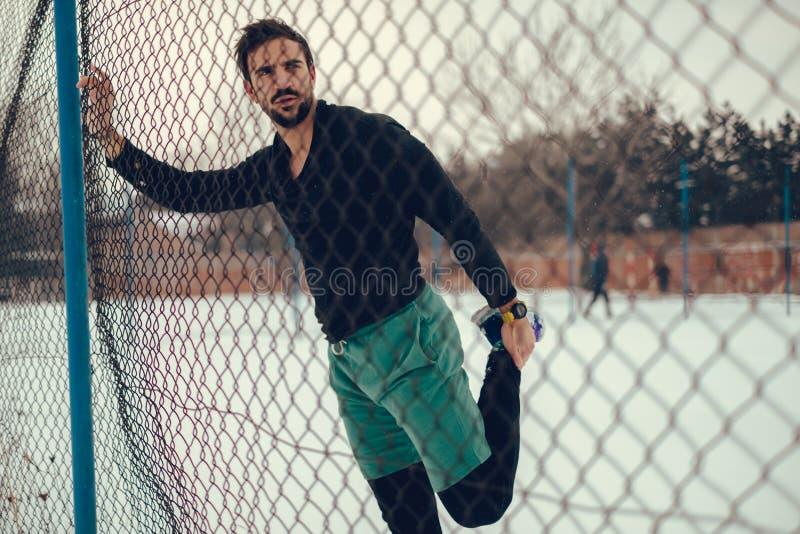 Idrottsman nen som sträcker quadriceps på staketet på en snöig dag arkivfoton