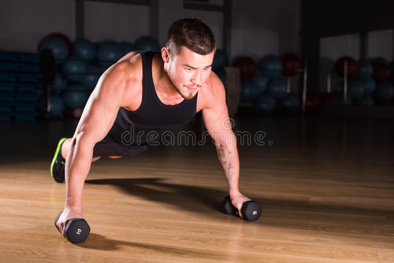 Idrottsman nenDoing Pushups With för ung man hantlar som delen av bodybuildingutbildning royaltyfria foton