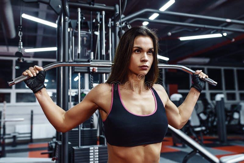 Idrottsman nenflicka i sportswear som utarbetar och utbildar henne armar och skuldror med övningsmaskinen i idrottshall arkivfoto