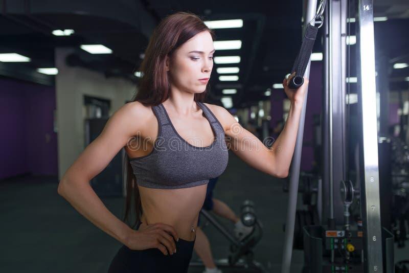 Idrottsman nenflicka i sportswear som utarbetar och utbildar henne armar och skuldror med övningsmaskinen i idrottshall royaltyfria bilder