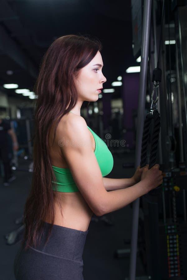 Idrottsman nenflicka i sportswear som utarbetar och utbildar henne armar och skuldror med övningsmaskinen i idrottshall arkivbild