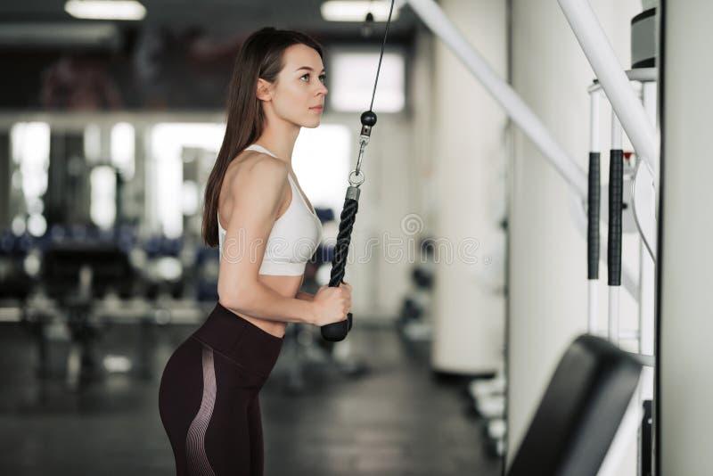 Idrottsman nenflicka i sportswear som utarbetar och utbildar henne armar och skuldror med ?vningsmaskinen i idrottshall royaltyfria foton