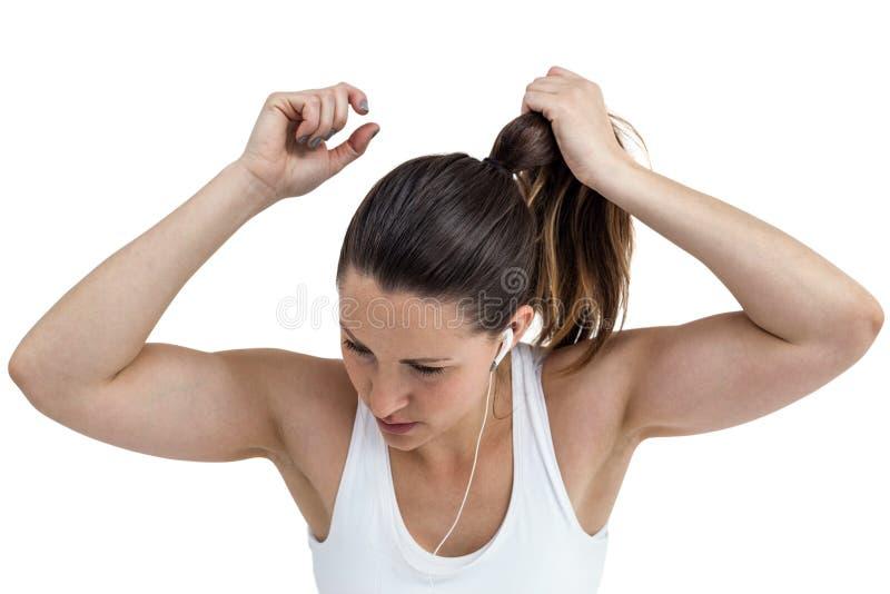 Idrottsman nenkvinna som binder hennes hår och lyssnar till musik royaltyfri bild