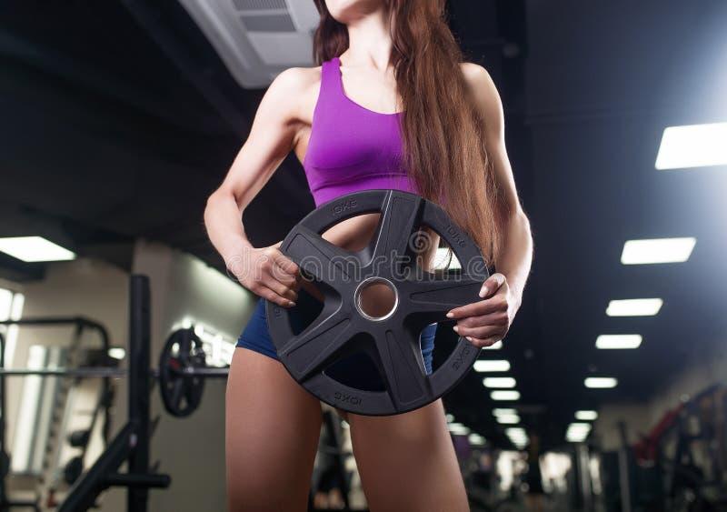 Idrottsman nenkvinna som utarbetar med skivstången Bikinikonditionflicka i sportswearen som gör övning i idrottshall royaltyfri foto