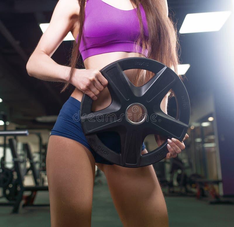 Idrottsman nenkvinna som utarbetar med skivstången Bikinikonditionflicka i sportswearen som gör övning i idrottshall arkivfoto