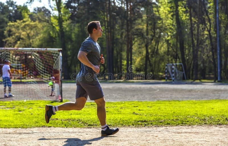 Idrottsman nenspring på idrotts- löparbana nära fotbollfält i skog royaltyfri foto