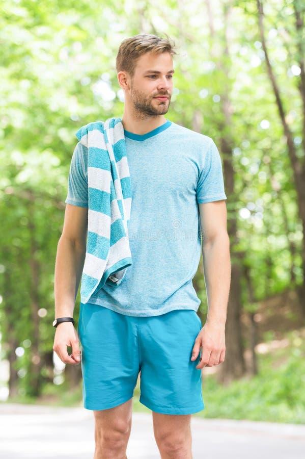 Idrottsman, precis når utbildning Man med handduken på naturligt landskap svettigt trött Sommarstrandtid och semester royaltyfri fotografi