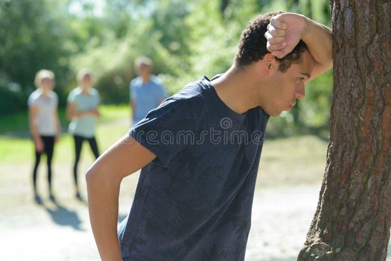 Idrottsman som lutar på träd för att få andedräkt tillbaka arkivfoto