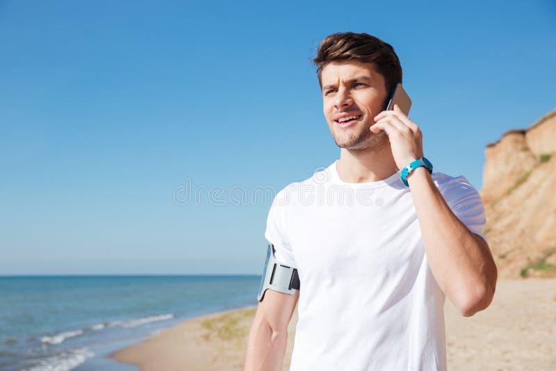 Idrottsman som talar på mobiltelefonen på stranden royaltyfri bild