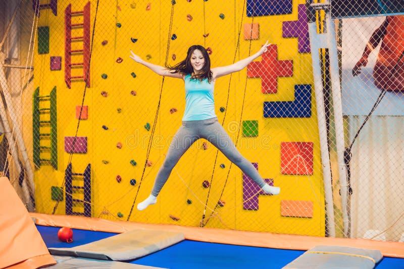 Idrottsmanbanhoppningen för ung kvinna på en trampolin i kondition parkerar och göra exersice inomhus fotografering för bildbyråer