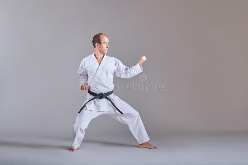 Idrottsmannen i karategi och med ett svart bälte gör formella karateövningar royaltyfri bild