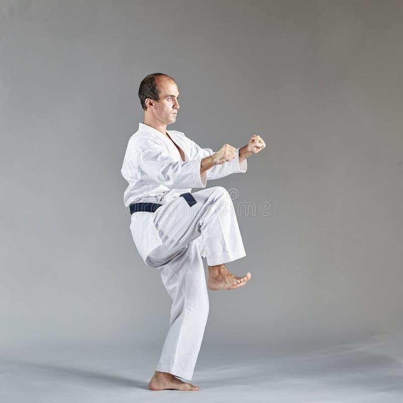 Idrottsmannen i karategi och med ett svart bälte utbildar formella karateövningar fotografering för bildbyråer