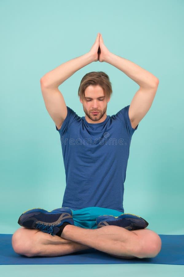 Idrottsmannen kopplar av i lotusblomma poserar Mannen mediterar på matt yoga Yoga för modeidrottsman nenövning i idrottshall Medi royaltyfri fotografi