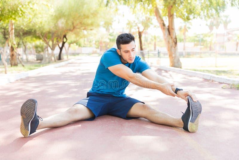 Idrottsmannen som gör sträcka övning för lopp på spår parkerar in royaltyfri fotografi