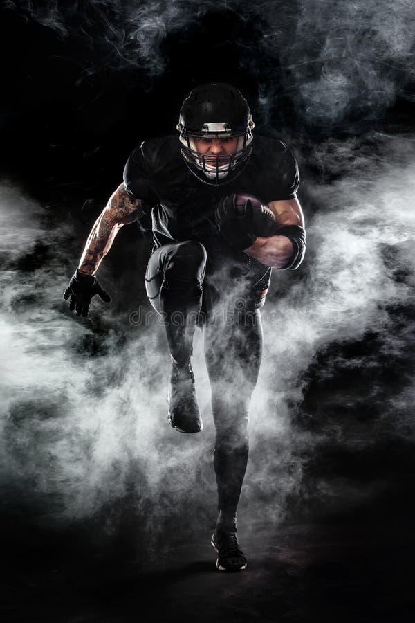 Idrottsmanspelare för amerikansk fotboll som isoleras på svart bakgrund royaltyfria bilder