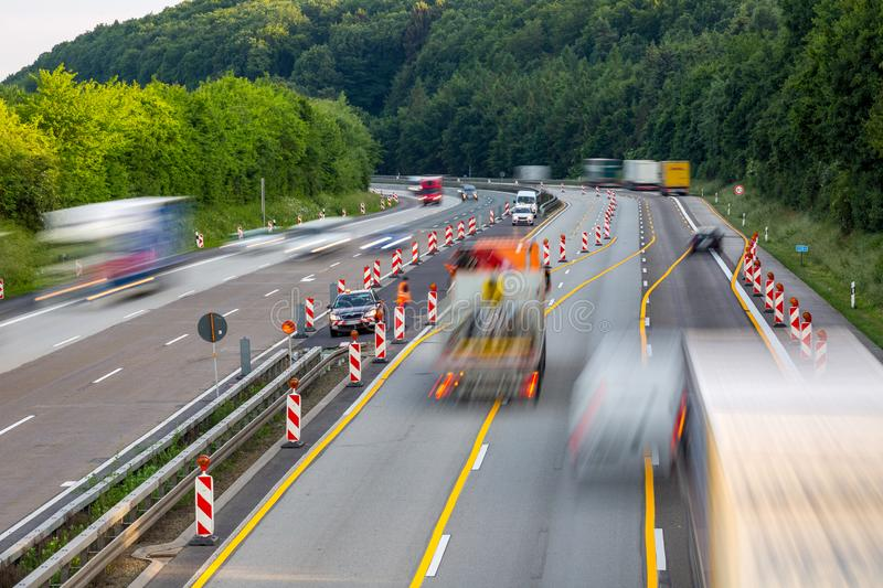 Autobahn highway construction site with passing trucks royalty free stock photo