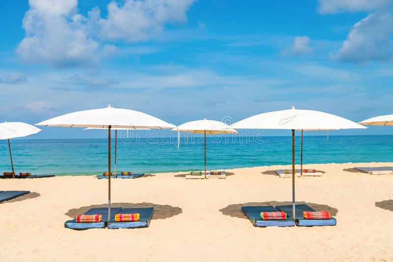 Idyllic beach relaxing concept with white parasols on sand. White idyllic beach parasol sunshade on sand beach with blue clear sea and a bit cloudy sky on stock photos