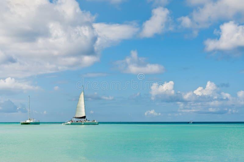 Idyllic blue beach with boats, Aruba island - Caribbean sea royalty free stock images