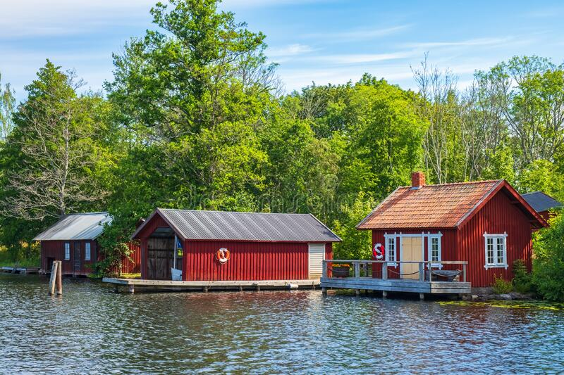 Idyllic cottage with jetty and boathouse on a lake stock images