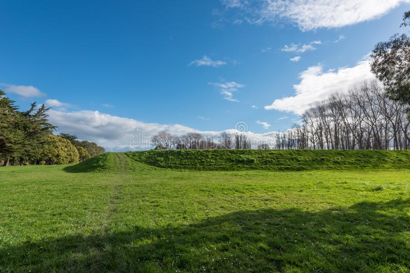 Idyllic countryside in Palmerston North New Zealand. With green meadows with trees in the background under a brilliant blue sky with clouds royalty free stock photography