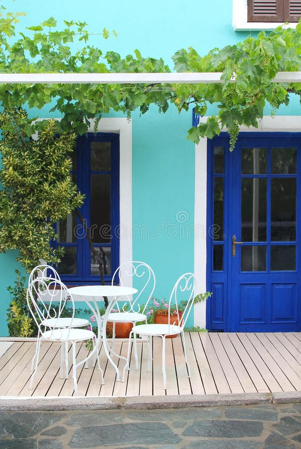 Romantic home garden patio white furniture, Greece. Idyllic garden patio with white furniture, wooden floor, flowerpots, turquoise wall and blue door, Chalkidiki stock photography