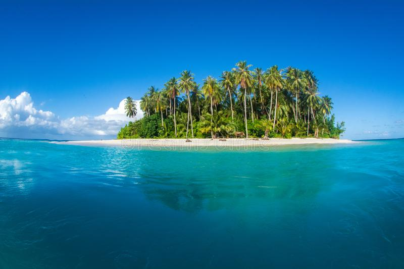 An idyllic island surrounded by the ocean in Indonesia. A beautiful idyllic little island surrounded by the ocean  in clear waters at far destination in stock photo