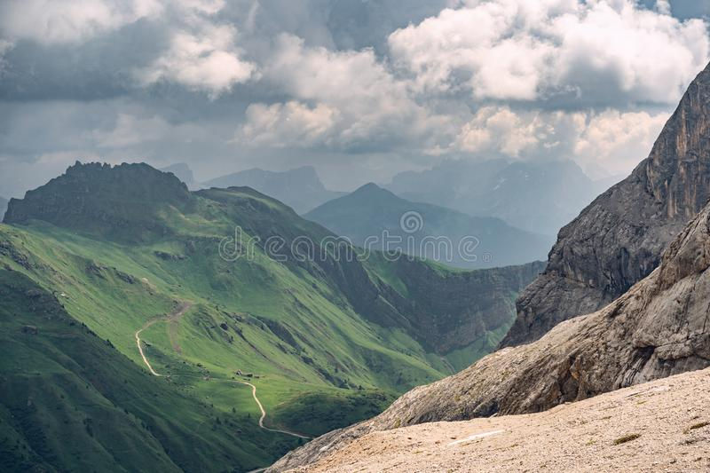 Idyllic landscape with green hill under cloud sky. Beautiful Alps with rocky mountain and green hill under cloud sky in national park royalty free stock photos
