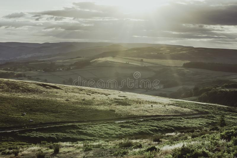 Idyllic landscape of Peak District National Park, Derbyshire, Uk. Afteroon sun shining over scenic mountain valley with hills and fields.Beautiful scenery of royalty free stock photography