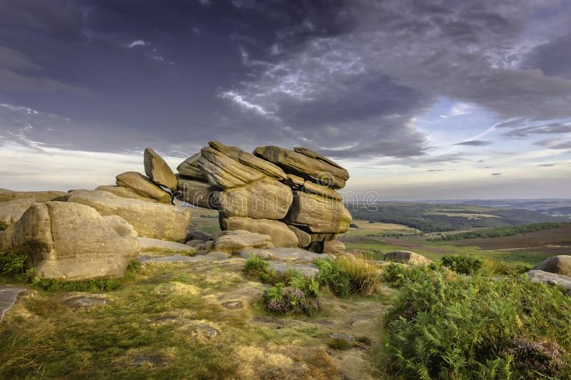 Idyllic landscape of Peak District National Park, Derbyshire, Uk. Sandstone rock formation on top of the hill lit by afternoon light and cloudy sky above royalty free stock photos
