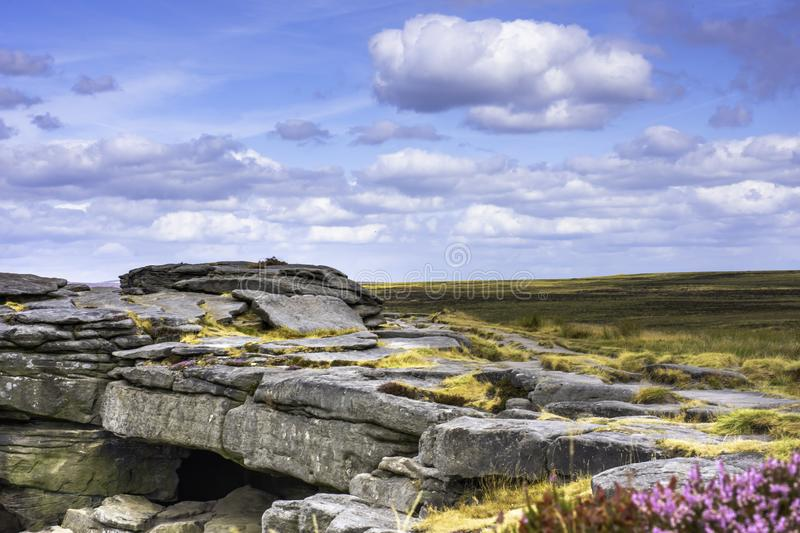 Idyllic landscape of Peak District National Park, Derbyshire, Uk. Sandstone rocks on top of the mountain ridge and blue sky with few clouds over horizon.Popular royalty free stock photos